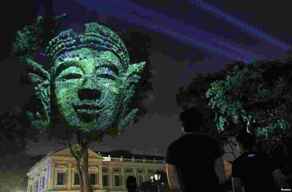 "People look at French artist Clement Briend's photographic light installation ""Divine Trees"", which features images of divine figures highly revered in Asian cultures projected on trees towering over bystanders, during a media preview of the Singapore Night Festival in Singapore."