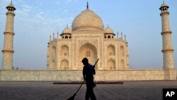 FILE - In this June 3, 2013, photo, a worker sweeps in front of Taj Mahal in Agra, India. A court in India has ordered a state government to remove a wood-burning crematorium from near the Taj Mahal to protect the iconic monument from pollution damage.