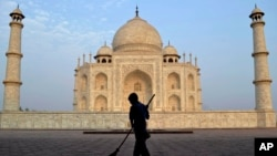 FILE - In this June 3, 2013, photo, a worker sweeps in front of Taj Mahal in Agra, India. Swarms of insects are proliferating in the heavily contaminated waters of the Yamuna River, which flows behind the 17th century monument.