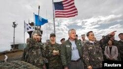 Bộ trưởng Quốc phòng Nam Triều Tiên Kim Kwan-jin hướng dẫn Bộ trưởng Quốc phòng Hoa Kỳ Chuck Hagel trong chuyến thị sát khu vực phi quân sự giữa 2 miền Nam, Bắc Triều Tiên