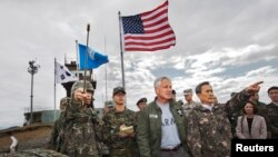 South Korean Defense Minister Kim Kwan-jin (R) points out a location in North Korea to U.S. Secretary of Defense Chuck Hagel, from Observation Point Ouellette during a tour of the Demilitarized Zone (DMZ), South Korea September 30, 2013.