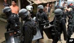 Para anggota Densus 88 membawa perlengkapan dan senjata mereka setelah melakukan penggerebekan di rumah yang ditempati oleh militan di Kabupaten Bandung, 8 Mei 2013. (Foto: dok).