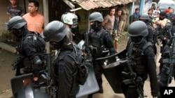 Para anggota Densus 88 membawa perlengkapan dan senjata mereka setelah melakukan penggerebekan di rumah yang ditempati oleh militan di Kabupaten Bandung, Mei 2013. (Foto: Dok)