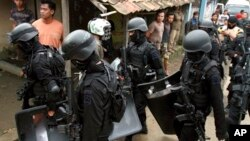 Para anggota Densus 88 membawa perlengkapan dan senjata mereka setelah melakukan penggerebekan di rumah yang ditempati oleh para tersangka teroris di Kabupaten Bandung, Rabu malam (8/5).