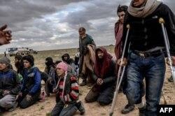 Muškarci i dječaci za koje se sumnja da su iz Islamske države, čekaju da ih pretresu pripadnici sirijskih demokratskih snaga (SDF) nakon što su napustili posljednje uporište u Baghouzu u sjevernoj pokrajini Deir Ezzor, 27. februar 2019.