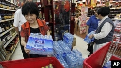 Customers stock cartons of bottled mineral water, after a local river which is the source of drinking water was polluted by a chemical leakage, at a supermarket in Hangzhou, Zhejiang province June 6, 2011. A tanker travelling along a highway overturned an