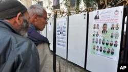 Passersby look at electoral campaign posters for the upcoming legislative election in Algiers, Algeria, April 9, 2017.