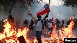 Un manifestante sostiene una bandera de Chile mientras está parado cerca de muebles en llamas durante una protesta contra el gobierno de Chile en Santiago, Chile, 18 de noviembre de 2019.