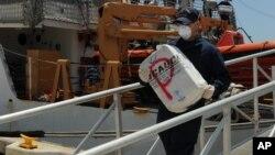 Un efectivo de la Guardia Costera de EE.UU. desembarca cocaína decomisada recientemente.