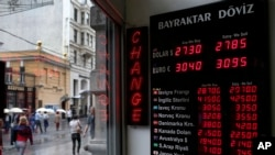 People walk past a currency exchange office in Istanbul, Turkey, June 8, 2015. The Turkish currency dropped to a record low against the dollar over the political uncertainty, trading at 2.8 lira against the dollar.