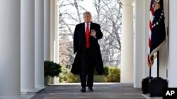 ປະທານາທິບໍດີສະຫະລັດ ທ່ານດໍໂນລ ທຣຳ ຍົກມືສົ່ງສັນຍານໃຫ້ ໃນຂະນະທີ່ທ່ານຍ່າງຜ່ານທາງເດີນ ໃນຫ້ອງ Oval Office ທີ່ທຳນຽບຂາວ, 25 ມັງກອນ 2019.