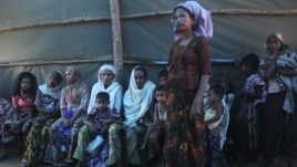 Shofica Belcom, 25, waits with other mothers at a Myanmar Red Cross health clinic near Sittwe, capital of Myanmar's Rakhine state, October 14, 2012.