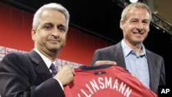 Juergen Klinsmann, of Germany, right, smiles after being introduced as the head coach of the U.S. men's soccer team by U.S. Soccer President Sunil Gulati, left, at a news conference in New York, Monday, Aug. 1, 2011.