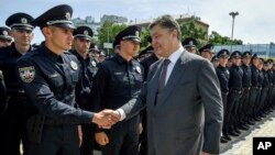 Ukrainian President Petro Poroshenko greets police officers at a swearing-in ceremony in Kyiv, Ukraine, July 4, 2015.