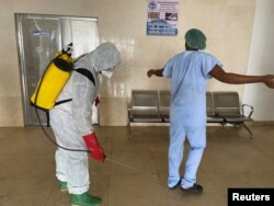 FILE - A health worker wearing protective equipment, disinfects a member of medical staff amid the spread of the coronavirus disease (COVID-19), at an hospital in Douala, Cameroon, April 27, 2020.
