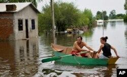 Một cặp vợ chồng chèo thuyền qua đường phố bị ngập lụt Durazno, Uruguay.