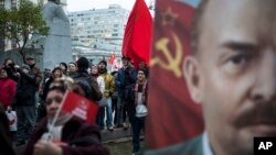 Communist Party supporters stand next to a monument to Karl Marx, left, and hold Soviet flags and portraits of Soviet founder Vladimir Lenin, right, during a demonstration marking the 100th anniversary of the 1917 Bolshevik Revolution in Moscow, Russia, Nov. 7, 2017.