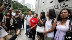 Bà Eman Villanueva (trái), Phó Chủ tịch Liên minh Công nhân nhập cư Philippines, và bà Dolores Balladares (thứ nhì từ bên trái), Chủ tịch của Liên hiệp người Philippines ở Hong Kong, cùng với các đại diện khác, gặp gỡ các nhà báo bên ngoài Tòa án Tối cao