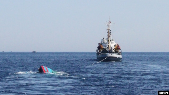 A Vietnamese sinking boat (L), which was rammed and then sunk by Chinese vessels near disputed Paracels Islands, is seen near a Marine Guard ship (R) at Ly Son island of Vietnam's central Quang Ngai province, May 29, 2014.