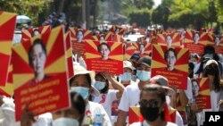 ក្រុមបាតុករប្រឆាំងនឹងរដ្ឋប្រហារយោធានាំគ្នាកាន់បដាមួយដែលមានរូបរបស់អ្នកស្រី Aung San Suu Kyi ខណៈដែលពួកគេប្រមូលផ្ដុំគ្នានៅខាងក្រៅការិយាល័យអង្គការសហប្រជាជាតិក្នុងទីក្រុងរ៉ង់ហ្គូន ប្រទេសមីយ៉ាន់ម៉ា ថ្ងៃទី១៤ ខែកុម្ភៈ ឆ្នាំ២០២១។