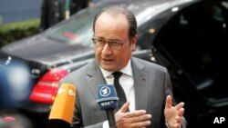 French President Francois Hollande speaks with the media as he arrives for an EU summit at the EU Council building in Brussels, Oct. 15, 2015.