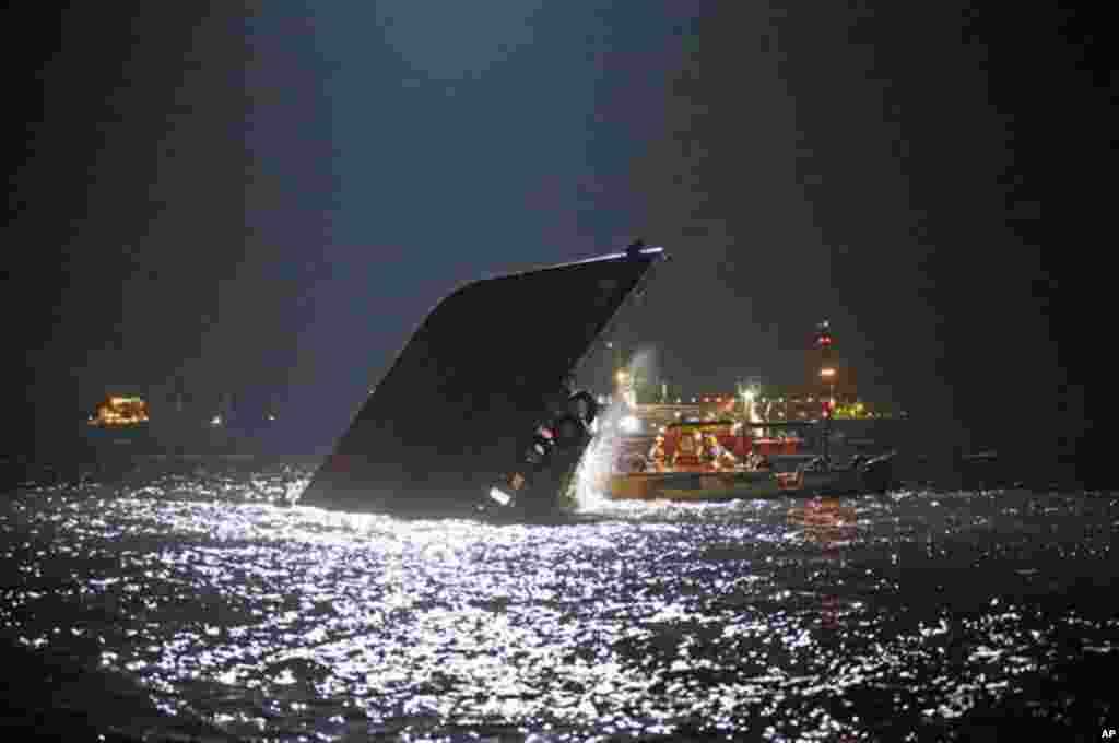 Rescuers check on a half submerged boat after it collided Monday night near Lamma Island, off the southwestern coast of Hong Kong Island, October 2, 2012.