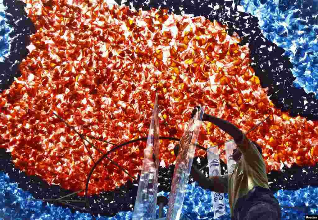 Một người chuẩn bị sân trình diễn tạm thời được xây dựng để phục vụ lễ hội Durga Puja ở Kolkata, Ấn Độ.