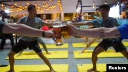 People participate in a beer yoga session, as the country eases the coronavirus disease (COVID-19) restrictions, at a craft brewery in Phnom Penh, Cambodia January 19, 2021. (REUTERS/Cindy Liu)