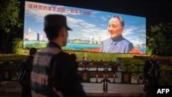 """2018年12月17日,在中国深圳,保安人员站在中国已故最高领导人邓小平的宣传牌前面,牌子上写着""""坚持党的基本路线一百年不动摇""""。"""