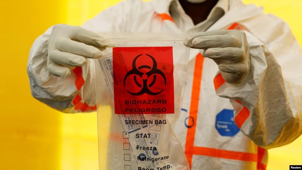 一名医务人员在展示新冠病毒检测试剂。
