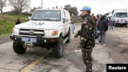 A Filipino United Nations peacekeeper stands next to a U.N. vehicle before it crosses from Israel into Syria at the Kuneitra border crossing on the Golan Heights, March 5, 2013.