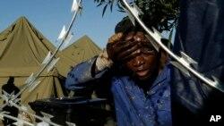 Un homme se lave le visage à l'extérieur d'un centre d'hébergement pour étrangers déplacés dans l'est de Johannesburg, Afrique du Sud, mardi 21 avril 2015.