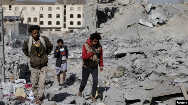 People walk on the rubble of a house destroyed by a Saudi-led airstrike in Yemen's capital, Sanaa, Jan. 29, 2016.