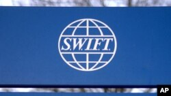 FILE - A sign for the Society for Worldwide Interbank Financial Telecommunications ( SWIFT) is seen outside the company headquarters in Brussels, Feb. 20, 2007.