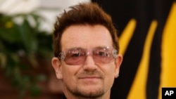 Irish singer Bono poses for media as he meets youth ambassadors of the ONE campaign together with with the President Joachim Gauck in Berlin, Oct. 8, 2012.