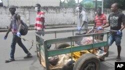 Những người tình nguyện ở Monrovia, Liberia đẩy chiếc xe chở một người đàn ông nghi bị nhiễm virut Eboal đến một trung tâm y tế