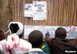 FILE - Congolese voters check their names on a list before casting their ballots in Bunia, eastern Democratic Republic of Congo, July 30, 2006.