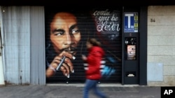 A woman walks past a mural depicting reggae music icon Bob Marley painted on the rolling shutter of a Tobacco shop in Rome, Thursday, Nov. 28, 2018. (AP Photo/Gregorio Borgia)