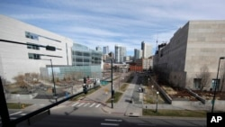 FILE - Normally bustling with folks heading to the city jail or courthouse, two people walk along the path between the two judicial complexes as the fear of coronavirus forces workers to stay home, in Denver, March 16, 2020.