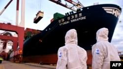 身穿防护服的中国海关人员在山东省青岛港检查一艘货轮。(2020年11月16日)