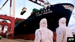 Petugas inspeksi imigrasi China mengenakan APD saat memeriksa kapal kargo di pelabuhan di Qingdao, di provinsi Shandong timur, China, 16 November 2020. (Foto oleh STR / AFP)