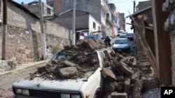 Một chiếc xe đậu trên đường bị hư hại vì bức tường sập trong trân động vào sáng thứ sáu ở ở Mexico, 18/4/14