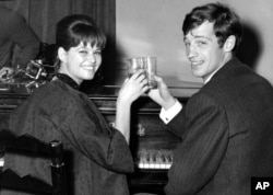 FILE - French actor Jean-Paul Belmondo and Italian actress Claudia Cardinale attend a cocktail party in the Foreign Press Association in Rome, Nov. 3, 1960.
