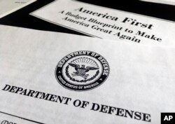 FILE - A portion of President Donald Trump's first proposed budget, focusing on the Department of Defense, and released by the Office of Management and Budget, is photographed in Washington, March 15, 2017.