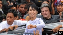 Burma opposition leader Aung San Suu Kyi (C) waves to the crowd as she leaves National League for Democracy (NLD) headquarters after addressing journalists and supporters in Yangon on April 2, 2012.