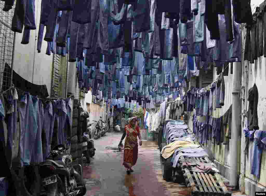 A woman walks through an alley as used pairs of jeans are hung to dry before they are sold in a second-hand clothes market in Kolkata, India.