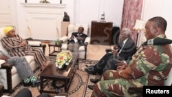 President Robert Mugabe, center, in a meeting with the ZDF Commander General Constantino Chiwenga, South African Minister of Defense Nosiviwe Mapisa-Nqakula (in yellow head wear), Zimbabwe Defense Minister Dr Sydney Sekeramayi and Zimbabwe State Security Minister Cde Kembo Mohadi at State House in Harare, Zimbabwe, Nov. 16, 2017.