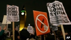 Protesters hold placards protesting a call for Britain to launch airstrikes on the Islamic State group inside Syria, during a demonstration outside Parliament ahead of a vote in London, Dec. 2, 2015.