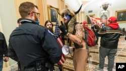 FILE - Supporters of President Donald Trump are confronted by U.S. Capitol Police officers outside the Senate Chamber inside the Capitol in Washington, Jan. 6, 2021. The Arizona man seen in the fur hat, Jacob Chansley, was taken into custody Jan. 9.