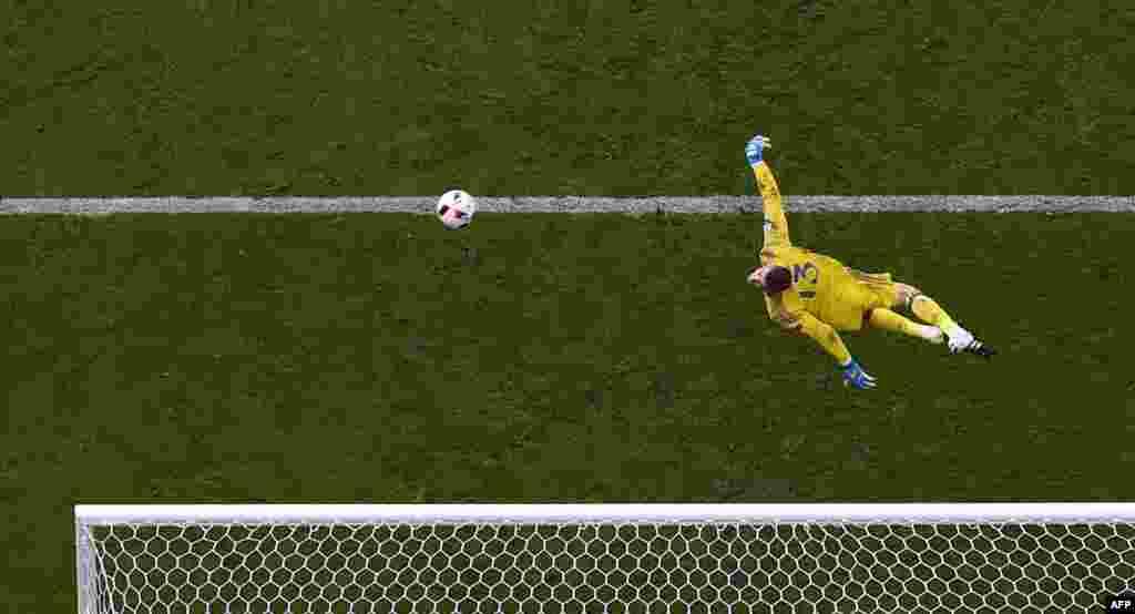 អ្នកចាំទីរបស់ក្រុមជម្រើសជាតិអេស្ប៉ាញកីឡាករ David De Gea លោតទះបាល់ចេញនៅអំឡុងពេលប្រកួតវគ្គជម្រុះ ១៦ក្រុមចុងក្រោយនៃការប្រកួតបាល់ទាត់ Euro 2016 រវាងក្រុមជម្រើសជាតិអ៊ីតាលី និងអេស្ប៉ាញនៅកីឡាដ្ឋាន Stade de France ក្នុងក្រុង Saint-Denis ជិតក្រុងប៉ារីស ប្រទេសបារាំង។